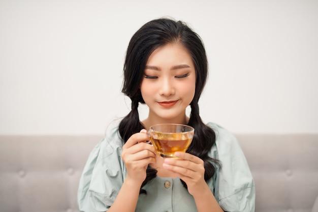 Mooie vrouw thee drinken uit beker