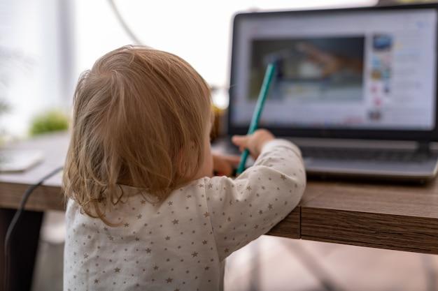 Mooie vrouw thuis in de keuken gebruikt een laptop en doet online aankopen met een creditcard via internet
