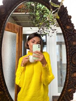 Mooie vrouw thuis maakt foto-selfie in spiegel op mobiele telefoon voor verhalen en berichten op sociale media, met een gezellige warme gele trui