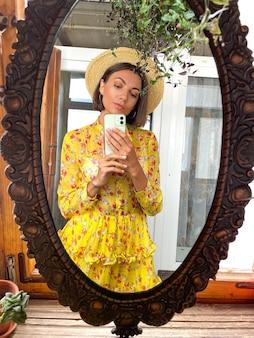 Mooie vrouw thuis maakt foto-selfie in spiegel op mobiele telefoon voor verhalen en berichten op sociale media, met felgele zomerjurk en hoed