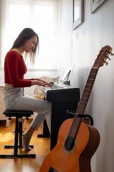 Mooie vrouw thuis piano spelen