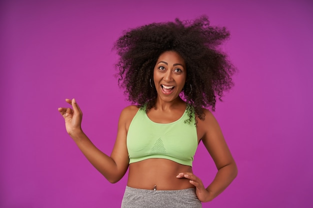 Mooie vrouw toont haar aangename emoties op paars, draagt een lichtgroene sportieve top, lacht vrolijk met brede mond open, houdt een handpalm om de taille en tilt de andere op