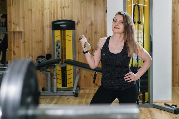 Mooie vrouw training in sportschool doen dumbbell press