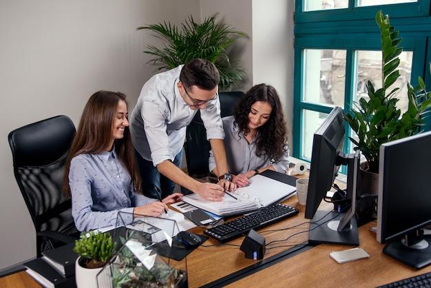 Mooie vrouw twee die aan het architectenproject werkt in het moderne bureau terwijl de mens in modieus overhemd documentomslagen brengt.