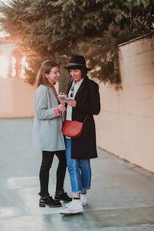Mooie vrouw twee die met toevallige kleding bij zonsondergang glimlachen en mobiele telefoon met behulp van. achterlicht. stad achtergrond