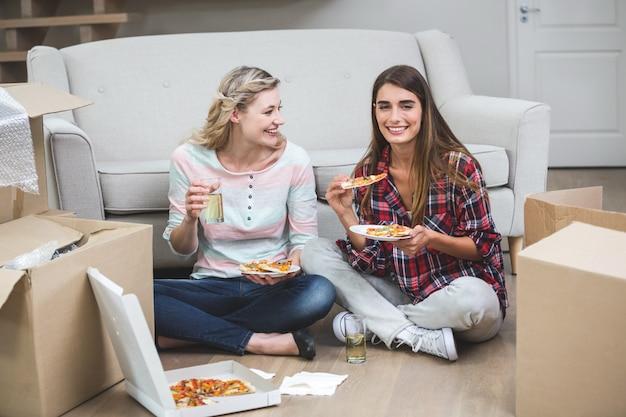 Mooie vrouw twee die pizza in het nieuwe huis heeft