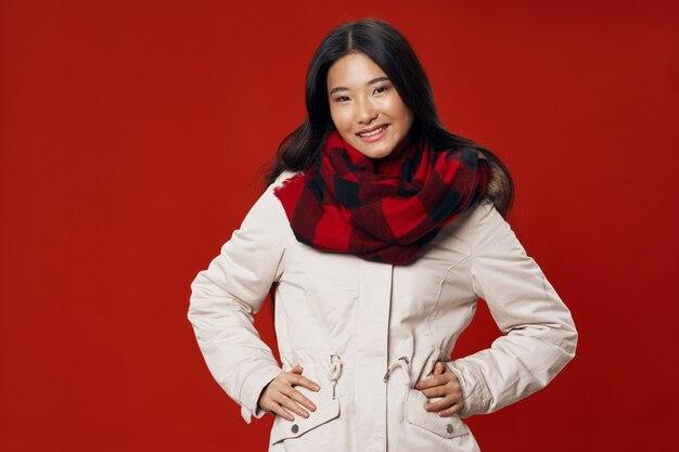 Mooie vrouw van aziatische uitstraling in een warm jasje en een sjaal om haar nek