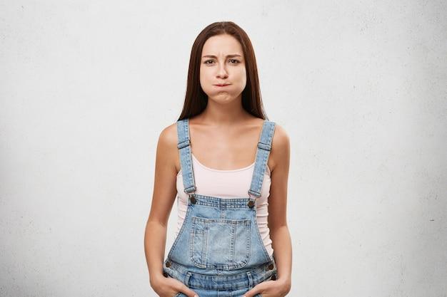 Mooie vrouw van europese verschijning gekleed in denim jumpsuit houdt haar adem in, doet haar best om niet te lachen.