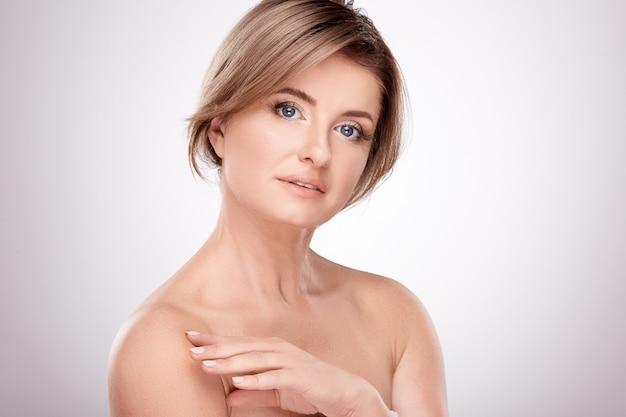 Mooie vrouw van gemiddelde leeftijd met naakt make-up en naakte schouders poseren muur, schoonheid foto concept, huid en rimpels behandeling, close-up.