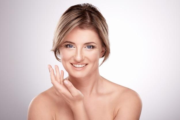 Mooie vrouw van gemiddelde leeftijd met naakt make-up en naakte schouders poseren muur, schoonheid foto concept, huid en rimpels behandeling