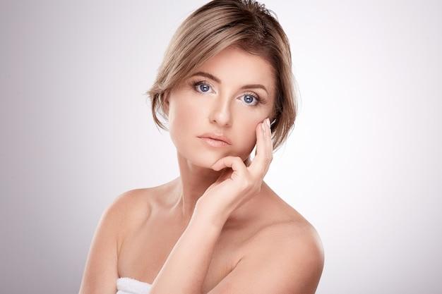 Mooie vrouw van gemiddelde leeftijd met naakt make-up en naakte schouders poseren muur, schoonheidsfoto concept, huid en rimpels behandeling, portret.