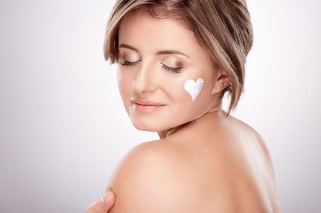 Mooie vrouw van gemiddelde leeftijd met naakte make-up en blote schouders, concept van schoonheidsfoto, behandeling van huid en rimpels, uv-bescherming, met crème, hartsymbool, gesloten ogen.