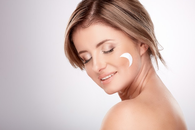 Mooie vrouw van gemiddelde leeftijd met naakte make-up en blote schouders, concept van schoonheidsfoto, behandeling van huid en rimpels, uv-bescherming, met crème, nachtcrème.