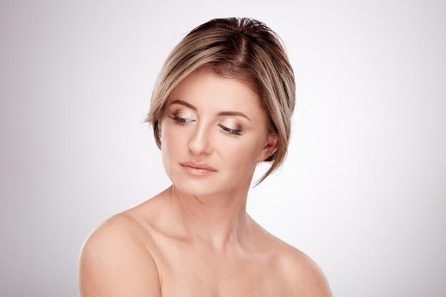 Mooie vrouw van gemiddelde leeftijd met naakte make-up en naakte schouders poseren muur, schoonheidsfoto concept, huid en rimpels behandeling.