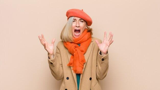 Mooie vrouw van hoge of middelbare leeftijd die woedend schreeuwt, zich gestrest en geïrriteerd voelt met handen in de lucht en zegt waarom ik