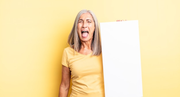 Mooie vrouw van middelbare leeftijd die agressief schreeuwt en er erg boos uitziet. leeg canvasconcept