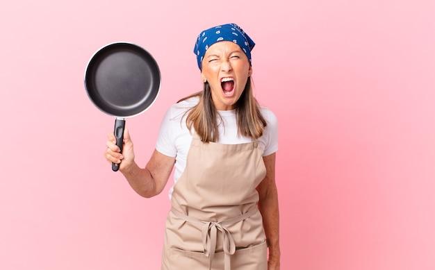 Mooie vrouw van middelbare leeftijd die agressief schreeuwt, erg boos kijkt en een pan vasthoudt. chef-kok concept