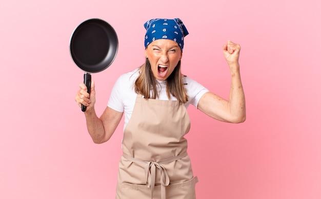 Mooie vrouw van middelbare leeftijd die agressief schreeuwt met een boze uitdrukking en een pan vasthoudt. chef-kok concept