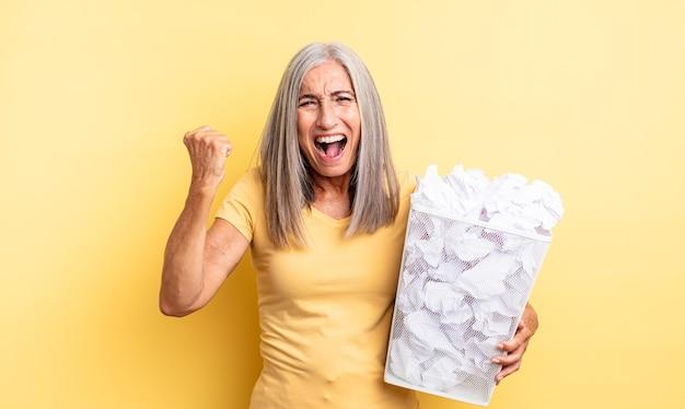 Mooie vrouw van middelbare leeftijd die agressief schreeuwt met een boze uitdrukking. papieren ballen mislukking concept