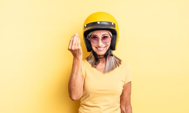 Mooie vrouw van middelbare leeftijd die capice of geldgebaar maakt en zegt dat je moet betalen motorhelm concept