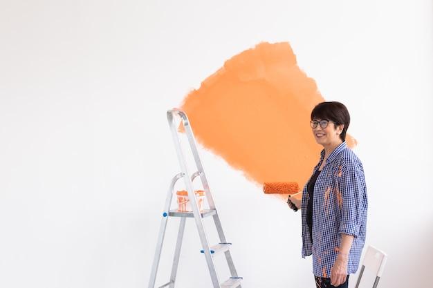 Mooie vrouw van middelbare leeftijd die de muur met verfroller schildert. portret van een jonge mooi