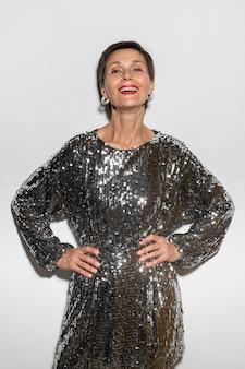 Mooie vrouw van middelbare leeftijd die een glanzende jurk draagt