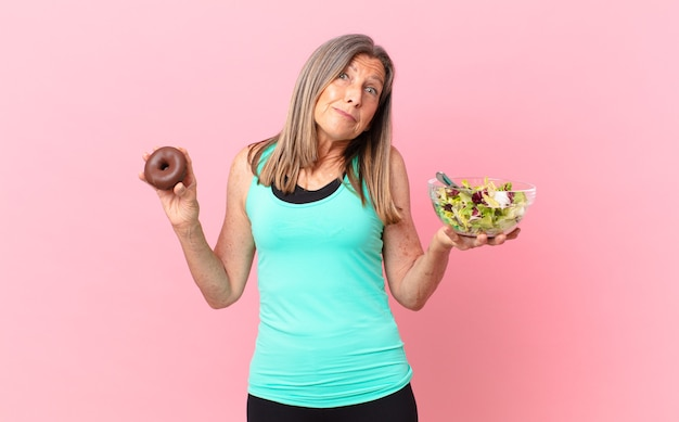 Mooie vrouw van middelbare leeftijd die een salade en een donut aan het koken is
