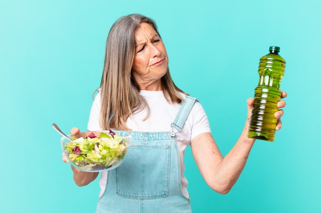 Mooie vrouw van middelbare leeftijd die een salade heeft.