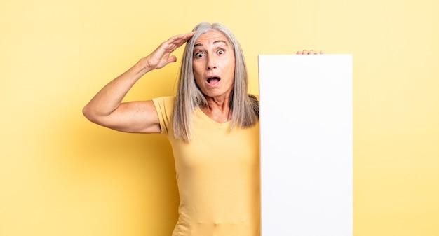 Mooie vrouw van middelbare leeftijd die er gelukkig, verbaasd en verrast uitziet. leeg canvasconcept