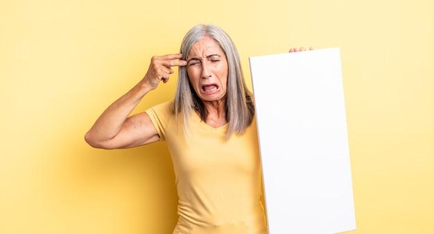 Mooie vrouw van middelbare leeftijd die er ongelukkig en gestrest uitziet, zelfmoordgebaar dat een pistoolteken maakt. leeg canvasconcept