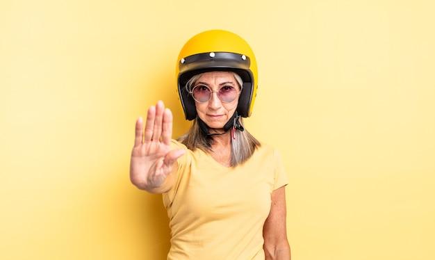 Mooie vrouw van middelbare leeftijd die er serieus uitziet en een open palm toont die een stopgebaar maakt. motorhelm concept