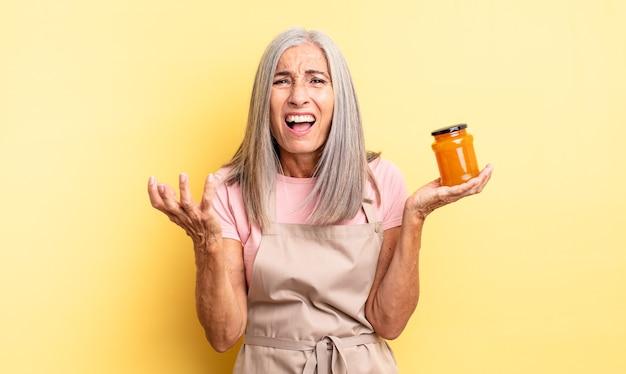 Mooie vrouw van middelbare leeftijd die er wanhopig, gefrustreerd en gestrest uitziet. perzik jam