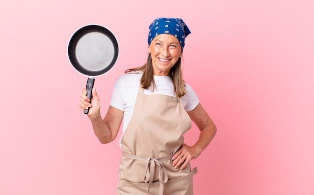Mooie vrouw van middelbare leeftijd die gelukkig lacht met een hand op de heup en zelfverzekerd en een pan vasthoudt. chef-kok concept