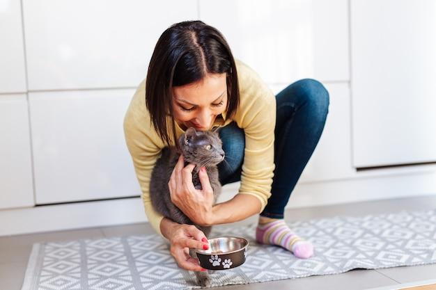 Mooie vrouw van middelbare leeftijd die haar kat thuis voedt.