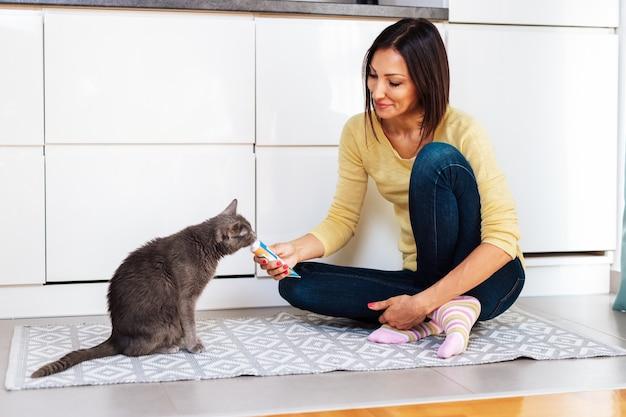 Mooie vrouw van middelbare leeftijd die haar kat thuis voedt