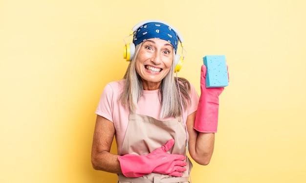 Mooie vrouw van middelbare leeftijd die hardop lacht om een of andere hilarische grap. schuursponsje reiniger