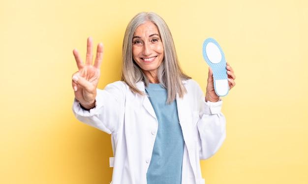 Mooie vrouw van middelbare leeftijd die lacht en er vriendelijk uitziet, met nummer drie. pedicure concept