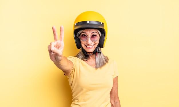Mooie vrouw van middelbare leeftijd die lacht en er vriendelijk uitziet, met nummer twee. motorhelm concept