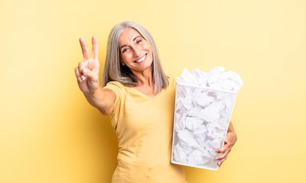 Mooie vrouw van middelbare leeftijd die lacht en er vriendelijk uitziet, met nummer twee. papieren ballen mislukking concept