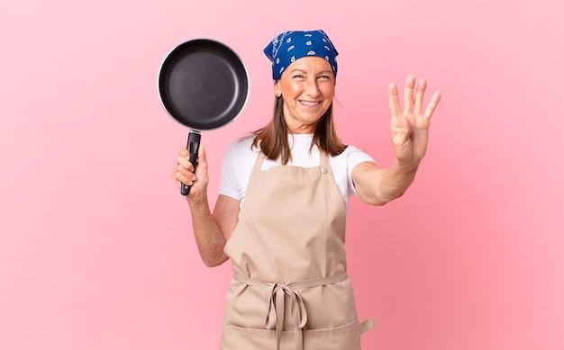Mooie vrouw van middelbare leeftijd die lacht en er vriendelijk uitziet, nummer vier toont en een pan vasthoudt. chef-kok concept