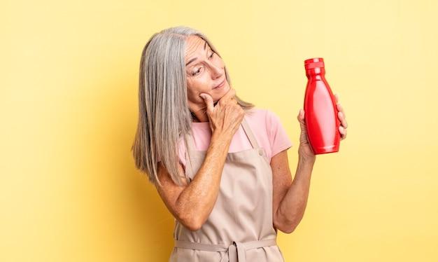 Mooie vrouw van middelbare leeftijd die lacht met een gelukkige, zelfverzekerde uitdrukking met de hand op de kin. ketchup-concept