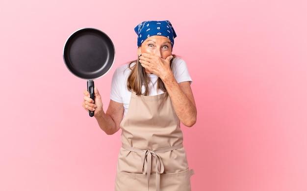 Mooie vrouw van middelbare leeftijd die mond bedekt met handen met een geschokt en een pan vasthoudt. chef-kok concept