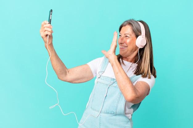 Mooie vrouw van middelbare leeftijd die muziek luistert met een koptelefoon