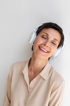 Mooie vrouw van middelbare leeftijd die naar muziek luistert via een koptelefoon