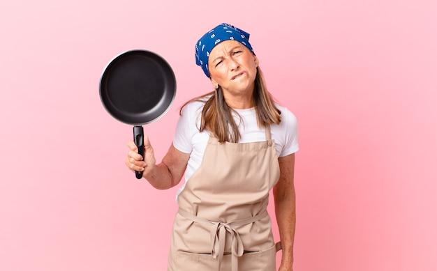 Mooie vrouw van middelbare leeftijd die verbaasd en verward kijkt en een pan vasthoudt. chef-kok concept