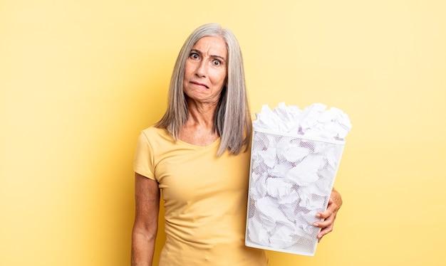 Mooie vrouw van middelbare leeftijd die verbaasd en verward kijkt. papieren ballen mislukking concept