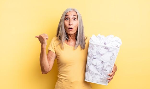 Mooie vrouw van middelbare leeftijd die verbaasd in ongeloof kijkt. papieren ballen mislukking concept