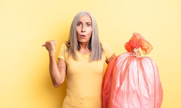 Mooie vrouw van middelbare leeftijd die verbaasd kijkt in ongeloof. plastic vuilniszak