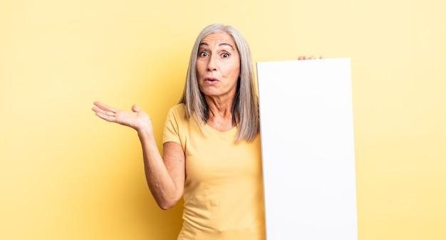 Mooie vrouw van middelbare leeftijd die verrast en geschokt kijkt, met open mond terwijl ze een object vasthoudt. leeg canvasconcept