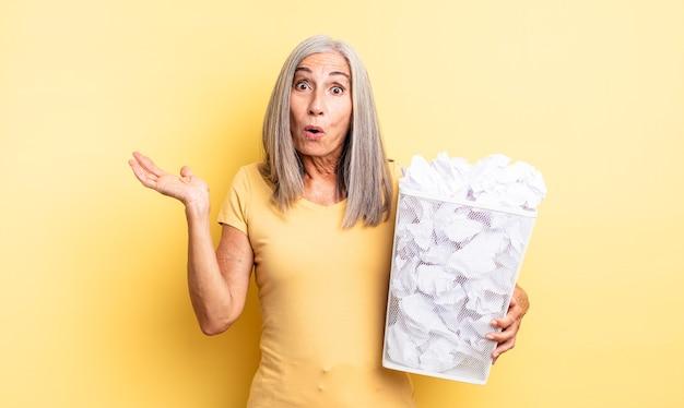Mooie vrouw van middelbare leeftijd die verrast en geschokt kijkt, met open mond terwijl ze een object vasthoudt. papieren ballen mislukking concept